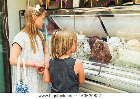Sweet little kids choosing dessert in ice cream shop