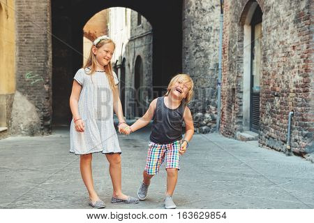 Two cute kids playing on the streets of Sienna, Italy. Little tourists visiting Europe, summer vacation