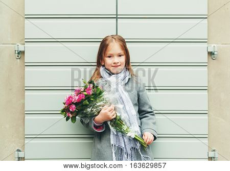 Outdoor portrait of 5-6 year old little girl wearing grey coat and scarf, holding bouquet of pink roses