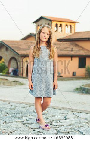 Summer portrait of 8-9 year old little girl wearing grey dress and purple flip flops