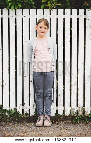 Fashion portrait of 7-8 year old little pretty girl wearing grey clothes, cardigan and trousers