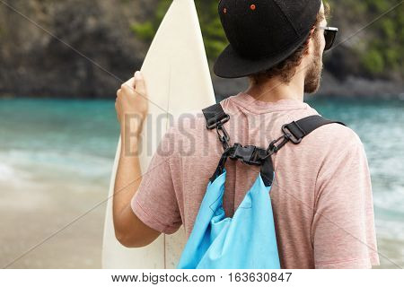 Rear View Of Young Bearded Beginner Surfer Wearing Snapback, Sunglasses And Blue Bag On His Shoulder