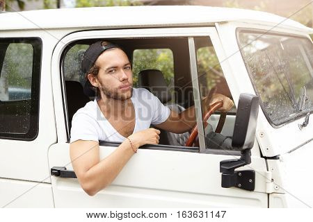Close Up Shot Of Fashionable Handsome Young Bearded Model Posing Inside White Jeep On Driver's Seat