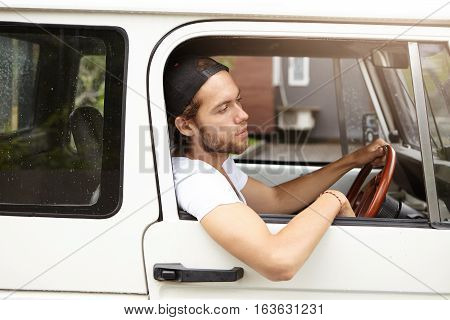 Side View Of Attractive Young Bearded Hipster Sitting On Driver's Seat While Driving His White Jeep