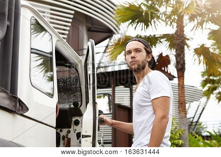 Outdoor Shot Of Handsome Young Bearded Man In T-shirt Standing Outside His White Crossover Utility V