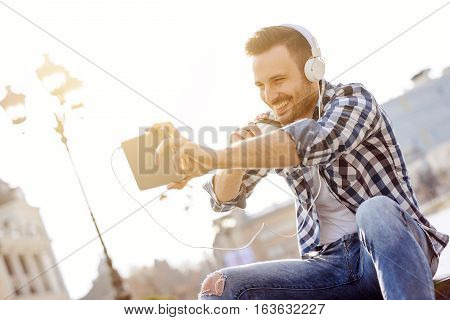 Portrait of smiling young man.Close up of a young man sitting outdoors listening to music.He is drinking coffee to go.