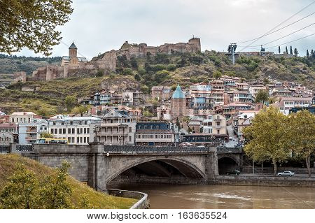 Georgia Tbilisi. View from the left bank of the Kura River in the Old Town Narikala Fortress Metekhi Bridge Cathedral of Saint George.
