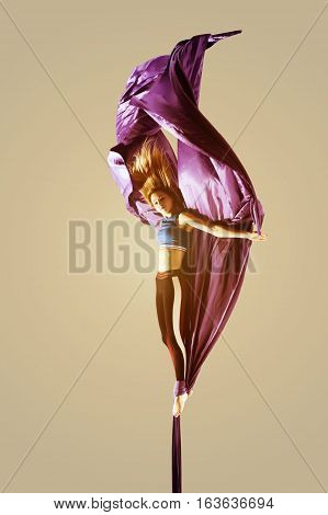 Girl hanging on aerial silk on isolated studio background. Acrobatics or gymnastics concept