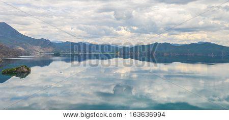 Single boat travels on mirror-like water at  Lugu Lake, Lijiang, China