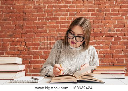 Student girl writing conspect free space. Young beautiful woman studying, reading textbook and noticing material to copybook. Education, learning, preparing for exam concept