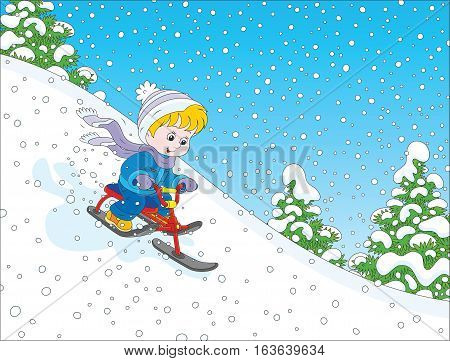 Little boy sliding down the snow hill on his small snow-scooter