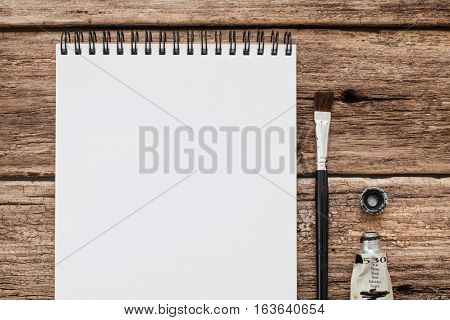 Tools for drawing on old wood flat lay mockup. Top view on blank sketchbook lying with paintbrush and tube of black paint on old wooden background. Art, imagination, hobby, illustration concept