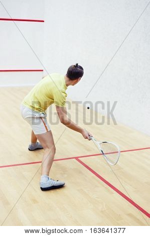 Back view of squash player in action reaching on squash court. Squash player in action on a squash court motion blurred image. Squash player hitting ball in squash court. Man playing match of squash alone. Photo with toning and selective focus