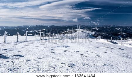 winter austrian mountains panorama with many mountain ranges, snow, wind turbines and blue sky with clouds from Pretulalpe hill in Fischbacher Alpen in Styria