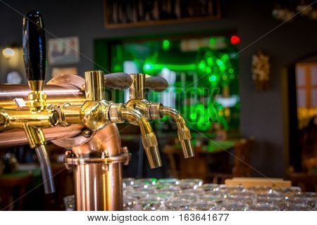Golden chrome draught taps in a bar