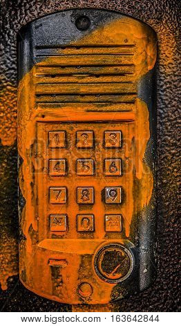 Intercom. Intercom panel on a metal door. Home security alarm. Password code security keypad system protection in public building, filled with paint, hooliganism