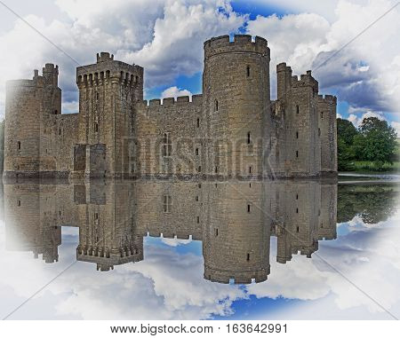 Historic Castle in the english countryside surrounded by a moat with a blue cloudy sky and vignetted edge, Sussex, England