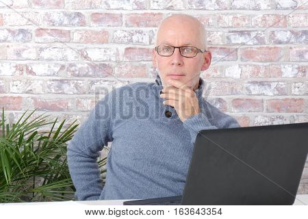 Portrait of a handsome mature man using laptop at office