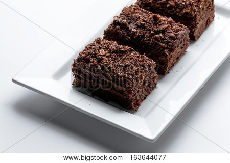 French Chocolate Napoleon cake of puff pastry with sour cream on a white plate close-up. Nutritious dessert. Selected Focus.