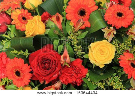 Wedding decorations in red orange and yellow: gerberas carnations and roses