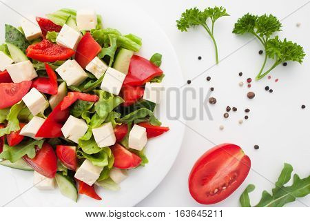 Fresh vegetable salad with feta cheese flat lay. Tasty vegetarian greek side dish on table with green and tomatoes. Healthy food, mediterranean cuisine, menu concept