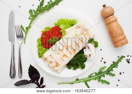 Shawarma on plate with cutlery and pepperbox. Traditional eastern burrito with fresh vegetables. Turkish sandwich, mediterranean cuisine, junk food concept
