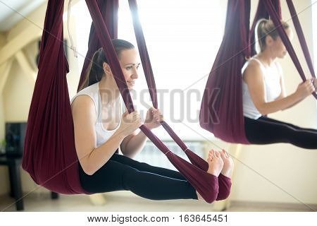 Two young yogi women doing aerial yoga practice in purple hammocks in fitness club. Beautiful happy females working out, performing antigravity yoga in class. Variation of seated forward bend, paschimottanasana pose