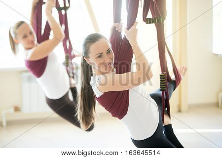 Two young attractive happy smiling yogi women doing aerial yoga practice in purple hammocks in fitness club. Beautiful females working out in class, performing antigravity yoga