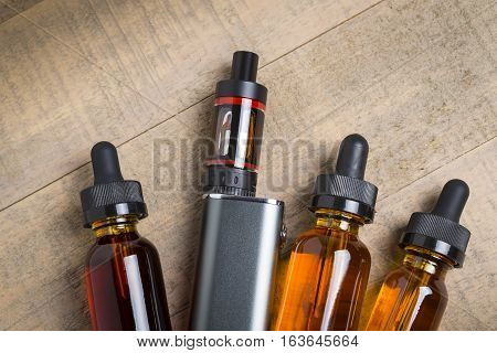 Vaping hardware and juice.  Vape e-juice with mod and bottles with child proof lids over wood background.