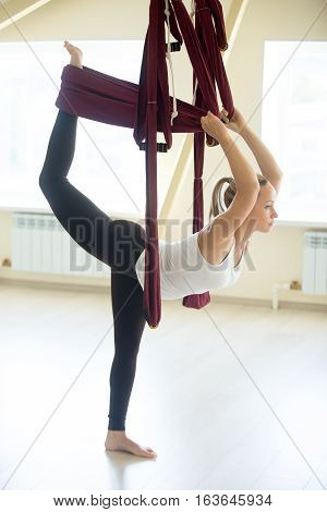 Young attractive yogi woman doing aerial yoga practice in purple hammock in fitness club. Beautiful model working out in class. Variation of Natarajasana, Lord of the Dance pose. Full length