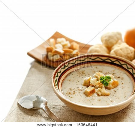 Soup and ingredients on the tablecloth isolated on white studio shot