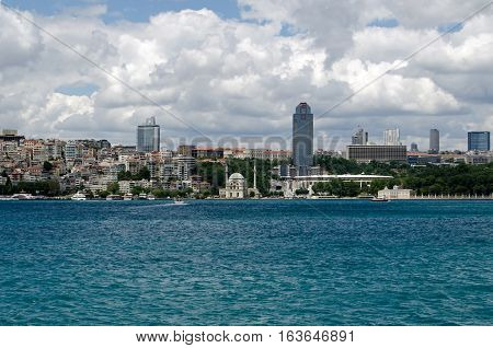 ISTANBUL TURKEY - JUNE 8 2016: View from the Bosphorus of the famous Besiktas football stadium in Istanbul. The Ritz Carlton Hotel is behind and the Dolmabahce Mosque is on the water front.