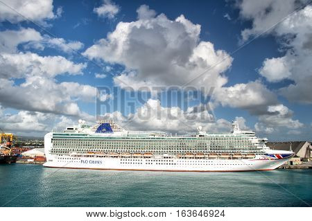 Port of Bridgetown Barbados - December 12 2015: Big cruise ship P&O Cruises in harbour with beautiful waterscape and cloudy sky horizontal picture