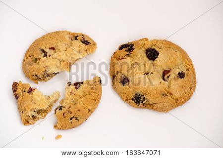 Two cookies with raisins broken into pieces.