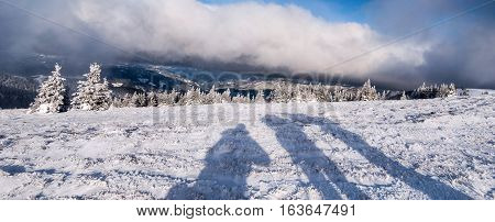 winter mountain meadow with small shrubs, hills on the background, shadows and blue sky with clouds bellow Stuhleck hill in Fischbacher Alpen mountains in Styria
