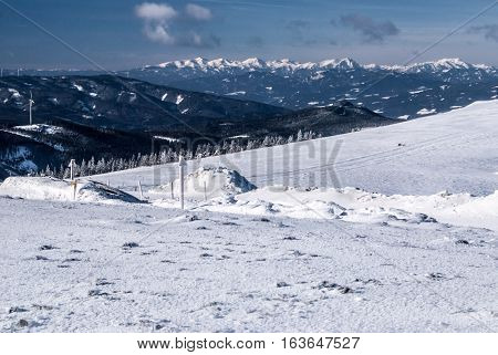 winter austrian Alps panorama with snow, mountain peaks and blue sky with clouds from Pretulalpe hill in Stuheck mountain ridge in Fischbacher Alpen mountain range in Styria