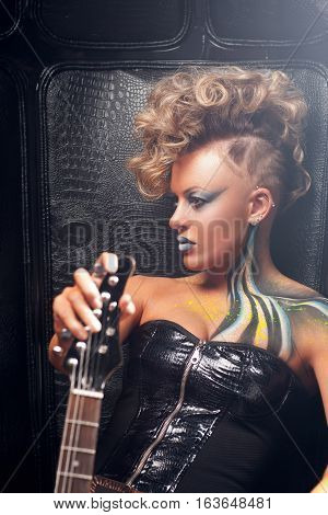 Beautiful woman punk with bass guitar profile. Attractive rocker girl in leather cloth, with bright body art and hairstyle, posing with her musical instrument. Subculture, lifestyle, fashion concept