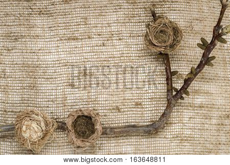 Three stylized birds' nests. Background beige burlap