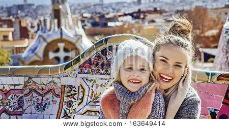 Mother And Daughter In Barcelona Hugging While Sitting On Bench