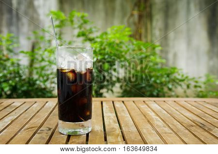 Glass of Ice coffee on wooden table in day light in garden with nature bakground.