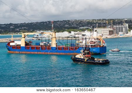 A tugboat leading a freighter out of Barbados harbor