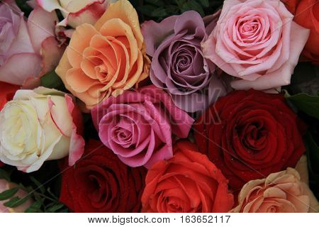 Roses in various bright colors in a mixed bridak bouquet