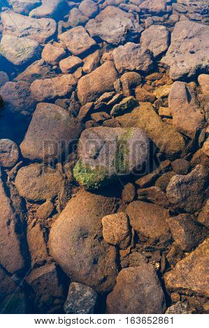Stony river bottom through transparent water different sizes of stones