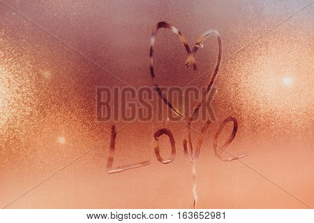 Inscription on steamy glass - heart symbol and love word valentine day concept