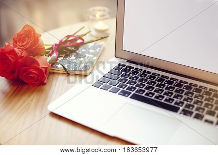 Open laptop computer with blank space for layout on a wooden table in cafe bar St. Valentines flowers note book during coffee break