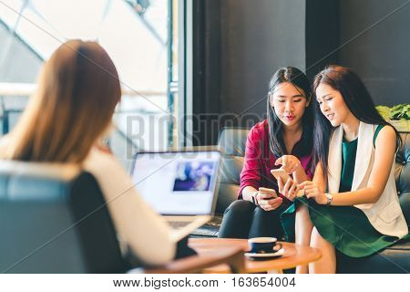 Beautiful Asian girls using smartphone and laptop chatting on sofa at cafe modern lifestyle with gadget technology or working woman on casual business concept