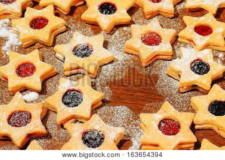 Christmas cookies in the shape of a star sprinkled with sugar on a brown wooden background