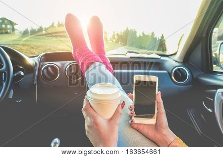 Young woman toasting coffee take away and looking smart cell phone with feet in warm socks on car dashboard - Freedoma and travel concept - Focus on paper cup hand - Warm raw filter