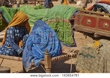NAGAUR, RAJASTHAN, INDIA - FEBRUARY 15, 2008: Women in brightly coloured clothing sitting on a bed, known as a charpoy, at the annual livestock fair in Nagaur, India.