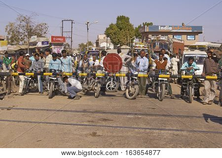 NAGAUR, RAJASTHAN, INDIA - FEBRUARY 16, 2008: Crowd of vehicles fill the road waiting for the barriers to rise at a level crossing in Nagaur, India.